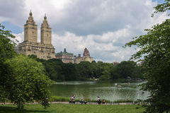 The Lake of Central Park New York City. People paddling in wood boats on The Lake of Central Park with its trees and the Eldorado twin tower building. Manhattan Stock Photo