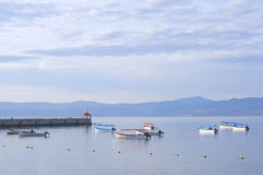 Lake Chapala Skiffs and Pier. Skiffs and fishing boats anchored in harbor off Lake Chapala pier in Chapala Mexico Royalty Free Stock Photo