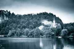 Lake and church. Bled, Slovenia. Popular touristic destination. Toned black and white monochrome image with grain Stock Images