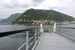 The lake and the city of Como. Ferry dock, in the background the funicular Como to Brunate where you can enjoy a splendid panorama of Como and its lake view Stock Photo