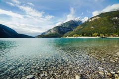 Mountain lake. Lake with clear clean water on a background of mountains. There are many pebbles under water. Blue sky with light clouds. Snow on the mountain Stock Photos