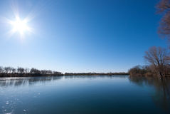 Lake and a cloudless sky. The picture shows a lake wich is partly covered with a thin layer of ice and a cloudless sky royalty free stock photography