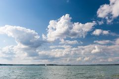 Lake and cloudscape and sailboat Royalty Free Stock Photo