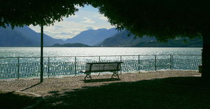 Lake Como. A bench in the sun facing Lake Como, Italy. The picture is taken in the town of Domaso, on the northwestern shore of the lake stock image