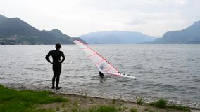 Young windsurfer trying to get on the sailing board. stock footage