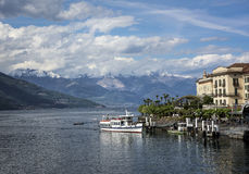 Lake Como, Italy. The public dock at Varenna on Lake Como with snow-capped mountains in the distance Stock Photo