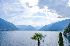 Lake Como from Villa del Balbianello view. Calm sunrays. Mountains and cloudy sky. Lenno, Italy royalty free stock photo