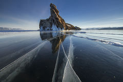 Lake is covered with a thick layer of ice. Ice story. Stone rock sticking out from under the piles of ice. Tcleanest lake in world Stock Photo