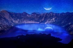 Lake in the crater of a volcano against the background of the starry sky. Reflection of the moonlight on the water. Indonesia. Rin. Jani volcano royalty free stock photography