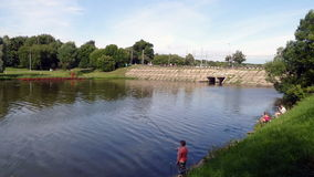 A lake with a dam and fishermen in the summer of stock video footage