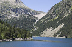 Lake and dam in the summer Pyrenees. Neouvielle nature reserve has many lakes and rich flora and fauna. The mountains are covered with dwarf mountain pines Royalty Free Stock Image