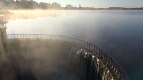 Lake dam with water splash and morning sunrise fog stock video footage