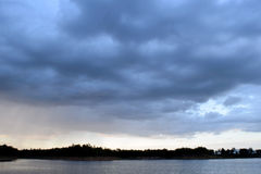 Lake and Dark blue stormy cloudy sky in evening Royalty Free Stock Images