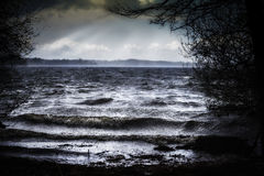 Lake with dark waves on the shore in bad stormy weather in the f Royalty Free Stock Photography