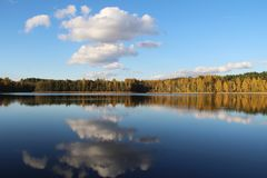 Lake in a delightful autumn forest at sunny day. Autumn trees with reflection. Russia. Lake in a delightful autumn forest at sunny day. Autumn trees with Royalty Free Stock Photos