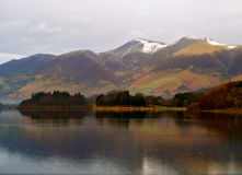 Lake Derwent in Winter. Lake Derwent in Cumbria, UK. Snow capped mountains in background Stock Photo