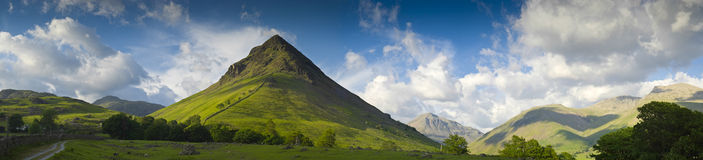 Lake District, Cumbria, UK. Dramatic mountain peak of Yewbarrow set against storm broken sky and warm hues of evening light, Lake District, Cumbria, UK Stock Photo