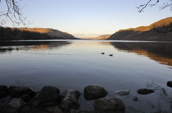 Lake district dawn, Ullswater. A calm winters view at dawn, of Ullswater, in the Lake district national park. Showing the shoreline in the foreground Royalty Free Stock Photos