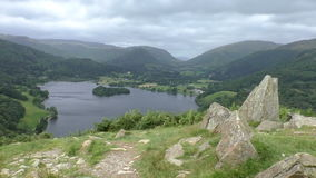 Lake District, England. Lake and mountain panorama. English Lake District national park scenery from top of the hill with stones on the grass foreground stock footage