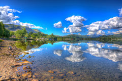 The Lake District England UK at Ullswater with mountains and blue sky on beautiful summer day with reflections in HDR Stock Photography