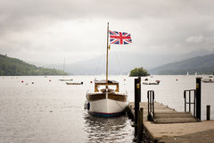 Lake district landscape. A boat with a Union Jack flag moored on a lake pier in the Lake District, UK Royalty Free Stock Images