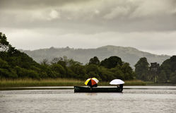 Lake district Llandscape. A small boat with fisherman holding colored umbrellas passes by on the lake in a gloomy rainy day. On the background the green Stock Photos