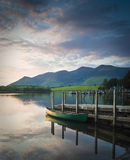 Lake District, UK. Idyllic english scene with traditional row boats reflected in a perfectly still Derwent Water and dramatic mountain backdrop, Lake District Stock Photo