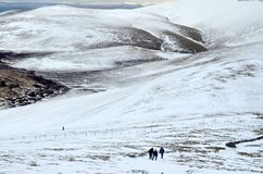 Lake District in winter. Hikers walking up snow covered Skiddaw mountain in winter, Lake District National Park, Cumbria, England Royalty Free Stock Photo