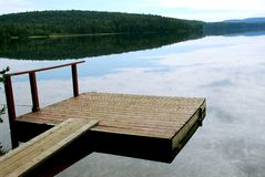 Lake dock. Old wooden boat dock on a beautiful lake in the evening stock photography