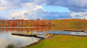 Lake with a dock and autumn forest. Autumn landscape on the lake with the cloudy sky, colorful trees of the forest and pier Royalty Free Stock Photography