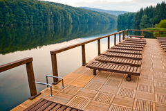 Lake dock and chairs. Wooden chair on lake dock at sunset Royalty Free Stock Images