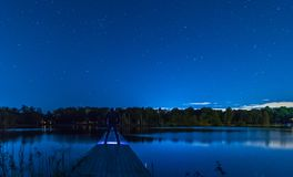 Lake dock at night. Stars ,water, dock, man with a flashlight on dock, stars Stock Images