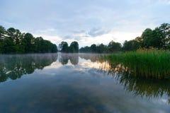 Lake. Durring foggy and cloudy sunrise Stock Photos