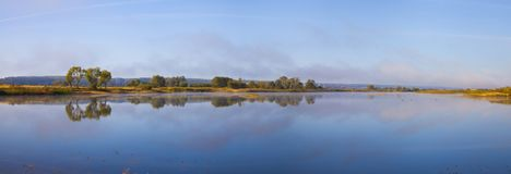 Lake early in the morning. Beautiful landscape. Lake early in the morning with a fog.Panorama Stock Photo