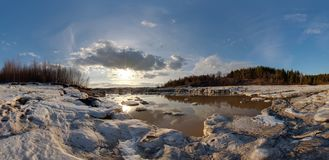 Lake. Early spring. Ice. Ice drift. Broken ice Clouds in the blue sky. Spring. The sun. Sunny weather. Panorama stock photo