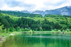The lake with emerald water is surrounded by coniferous forests and mountains. royalty free stock photography