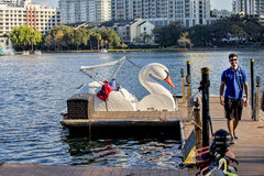 Lake Eola Swan Boats. A gondola-style swan boat is docked as a guide walks to welcome the next riders at this very busy attraction, at Lake Eola in Orlando Royalty Free Stock Photo