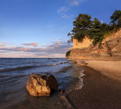 Lake Erie Cliffs. A Boulder Sitting In The Surf With Cliffs Behind Radiating Morning Light, Lake Erie At Barcelona Beach, New York, USA Stock Photography