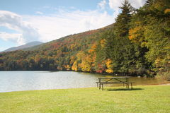 Lake fall scene with picnic table. An empty metal picnic table sitting on a grass field at a mountain lake, Lake Shaftsbury in Vermont, during the fall season Royalty Free Stock Photos