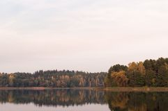 Lake and far shore at fall time. Faded colors and calm water gre Royalty Free Stock Photography