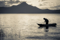 Lake fisherman on Boat Silhouette. Silhouette of a fisherman in a small boat on a lake. Black and white artistic Stock Photos