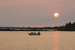 Lake fishing at sunset. Fishing from a boat on a lake at sunset Stock Photography