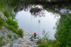 Lake in the foliage with a mermaid sitting on the shore royalty free stock image