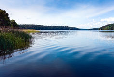 Lake in forest. Blue Lake water surface, rush and forest. Masuria Lakes District / Poland Stock Photography