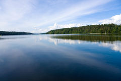 Lake in forest. View at the wide and calm Masurian lake surface in the forest, at sunny day. Blue cloudy sky Royalty Free Stock Photo