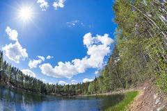 Lake in the forest with blue sunny sky Stock Photo