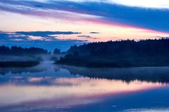 Lake and forest in a fog, landscape of wild nature at sunset. Wild nature after sunset befor night coming: lake and forest in a fog, sky blazing pink and blue stock photo
