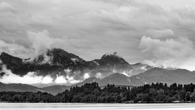 Lake forggen and alps. Black & white landscape from lake forggen over allgaeu woods to some alp mountains Stock Photos