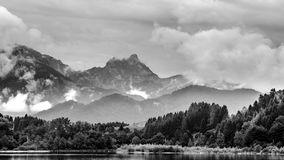 Lake forggen and alps. Black & white landscape from lake forggen over allgaeu woods to some alp mountains royalty free stock photo