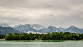 Lake forggen and alps. Landscape from lake forggen over allgaeu woods to some alp mountains Stock Images
